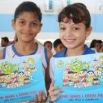Estudantes felizes apresentam cartilhas com o tema da ética e cidadania no currículo escolar